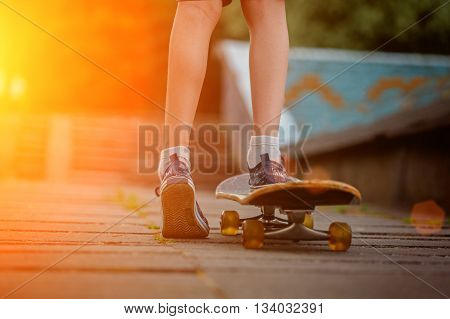Child feet with skateboard on the street at sunset light.