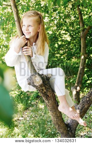 Little girl sitting on a tree and chatting his legs. Childhood