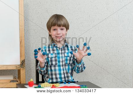 Blond boy sculpts from plasticine at home at the table. The idea and concept of the school school home education and developmental activities.