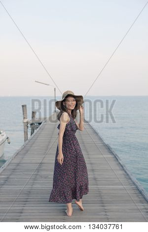 portrait of beautiful young woman wearing wide straw hat and long dress standing with happiness emotion on piers at sea beach