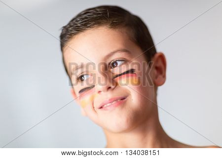 Portrait of a child with the flag of Germany painted on his face
