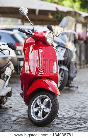 Rome Italy - May 27 2016: Old red Vespa parked on old street in Rome Italy.