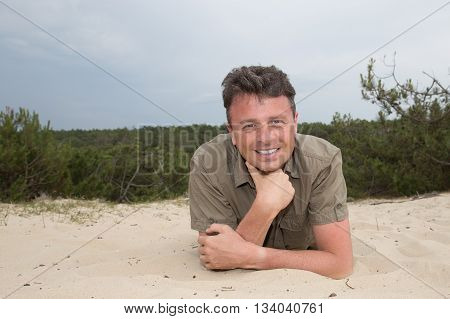 Man On Beach Lying In Sand Looking To Side Smiling