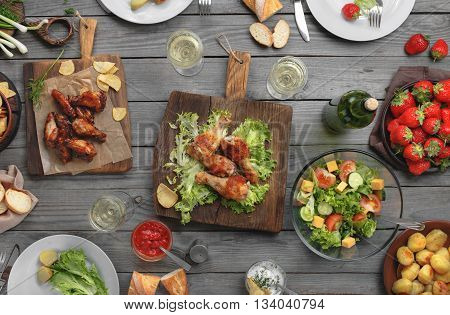 Different food cooked on the grill on a wooden table grilled chicken legs buffalo wings salad potatoes bottle of wine and three glasses of wine and strawberry top view. Outdoors Food Concept