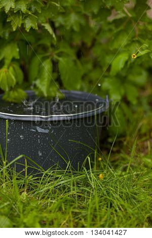 Collecting rainwater into a overflowing bucket in the grass