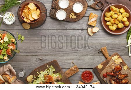Different food cooked on the grill on a wooden table with copy space grilled chicken legs buffalo wings salad potatoes beer and snack to beer. Outdoors Food Concept