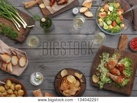 Different food cooked on the grill on a wooden table with copy space grilled chicken legs buffalo wings salad potatoes bottle of wine and three glasses of wine. Outdoors Food Concept