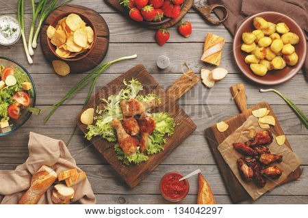 On the wooden table different food grilled chicken legs buffalo wings chips bread salad potatoes and strawberry top view. Outdoors Food Concept