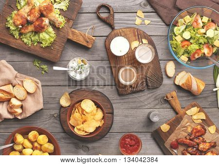 Different food cooked on the grill on a wooden table grilled chicken legs buffalo wings salad potatoes beer and snack to beer. Outdoors Food Concept