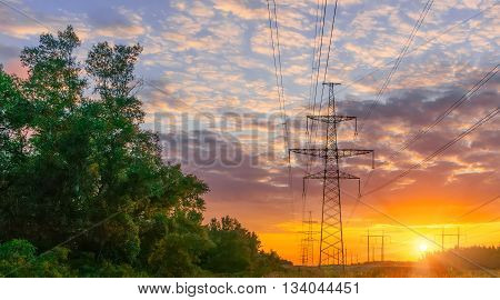 Scenery of silhouetted electrical tower during sunset.