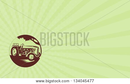 Business card showing illustration of a vintage farm tractor viewed from front set inside circle done in retro woodcut style.