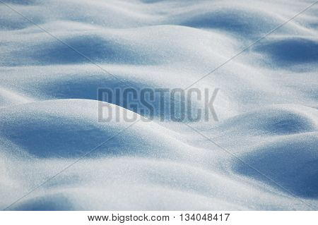 Background of wavy fresh snow with blue tint