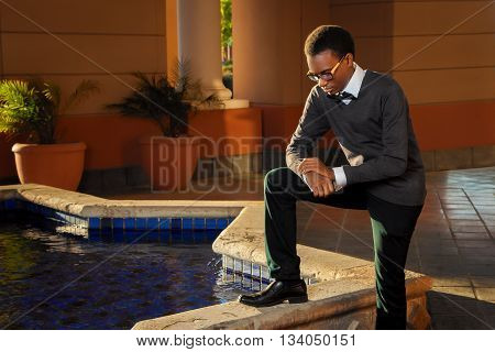 A young African American teenage male stands in a worshipful position by a fountain.