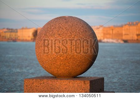 Granite ball on the spit of Vasilievsky island in the background of the Palace embankment in the light of the setting spring sun. Saint Petersburg, Russia
