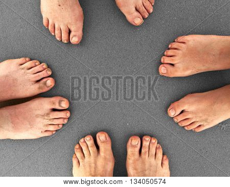 feet of family standing together at beach with grey sand