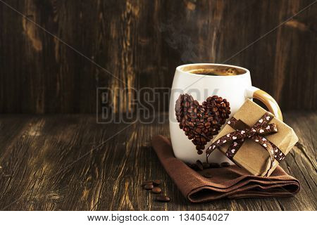 Hot coffee and gift box over wooden background. Vintage style. Space for text