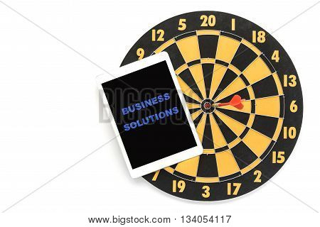 business solution words on tablet screen with dart target on bullseye over white background with copy space Goal target success business investment financial strategy concept abstract business background