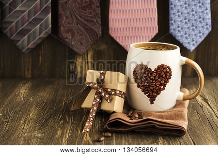 Happy Fathers Day Card. Mug of coffee, gift box and ties background. Vintage style. Toned image. Selective focus
