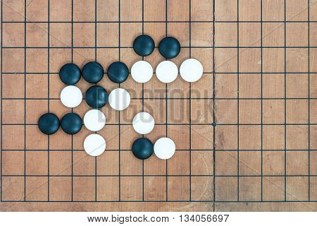 top view black and white stones playing with basic joseki in conner on go game board traditional chinese strategy board game sport hobby and recreation