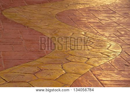 Yellow curvy tiled walkway on a background of orange tiles. Architectural background.