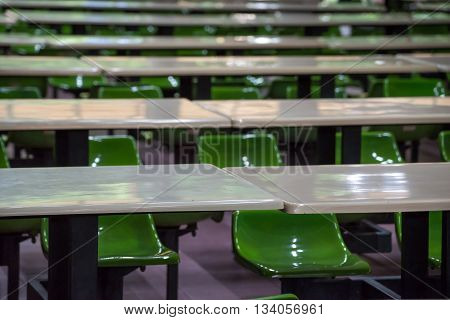 Rows of plastic tables and stools in a university cafeteria.