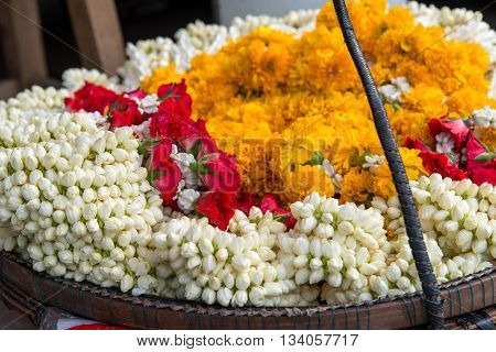 Garlands made of rose jasmine and marigold flowers for sale by a street hawker Bangkok Thailand.