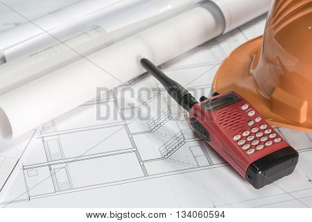radio communication with helmet and blueprint rolls over architectural blueprints architect engineering and contractor concept