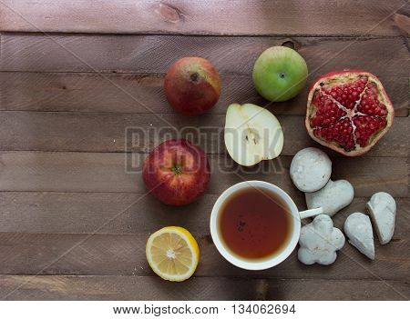 Garnets apples lemon cookies and a cup of tea on a wooden table