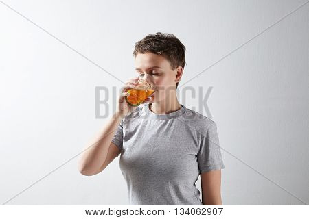 Beautiful sportywoman with healthly perfect skin in basic grey t-shirt dreamly drinking her fresh organic carrot orange juice with closed eyes