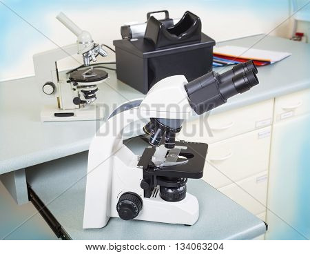Photo of a professional ocular laboratory microscope with stereo eyepiece in laboratory interior.