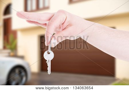 Male Hand Hanging House Key As Real Estate Concept