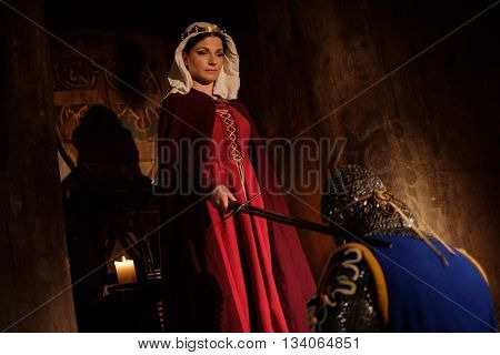 Medieval queen doing knighting ceremony in ancient castle interior.