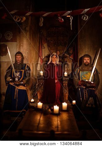 Medieval queen with her knights on guard in ancient castle interior.
