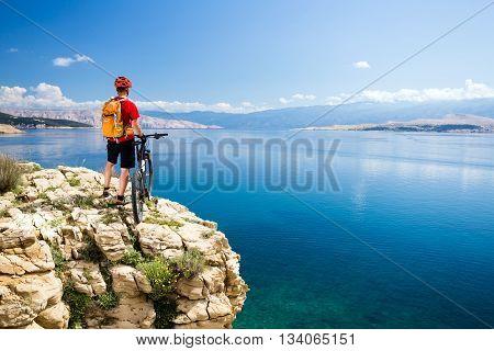 Mountain biking rider with bike looking at inspiring sea and mountains landscape. Man cycling MTB on enduro rocky trail path at sea side. Summer sport training fitness motivation and inspiration.