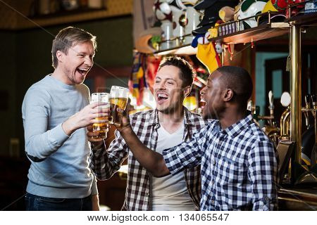 Smiling men with beer in pub