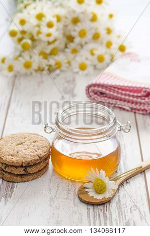 Honey can on wooden table as a concept of healty life