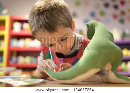 Child painting a ceramic pottery model dinosaur at school concept for art and creative education
