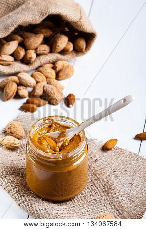 Homemade almond butter in a glass jar and a jute bag and napkin.