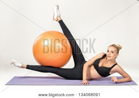 Young blonde woman training with fitball on the mat. Fitness exercises