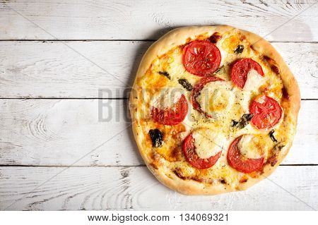 Pizza Margherita with tomatoes and mozzarella cheese on a white wooden surface