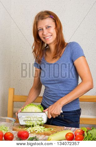 Woman cutting cabbage in kitchen