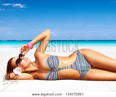 Beautiful woman on the beach, lying down on clean white sandy coast and with pleasure sunbathing, summer vacation on a tropical islands