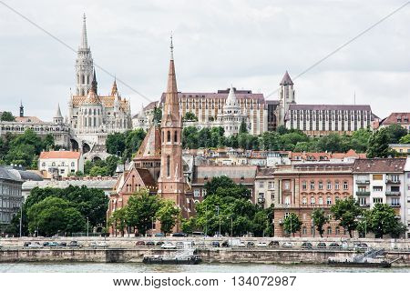 Matthias church Fishermans bastion and Calvinist church in Budapest Hungary. Cultural heritage. Architectural theme. Danube river bank. Greenery and old famous city.