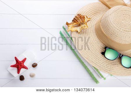 Beach accessories background on white wooden board
