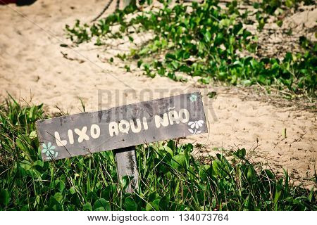 Wooden sign on the beach entrance which says