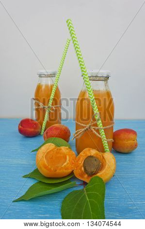 apricot juice in bottles with straws on a wooden table apricots background