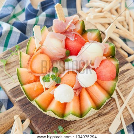 Fresh cantaloupe melon with mozzarella balls and smoked ham