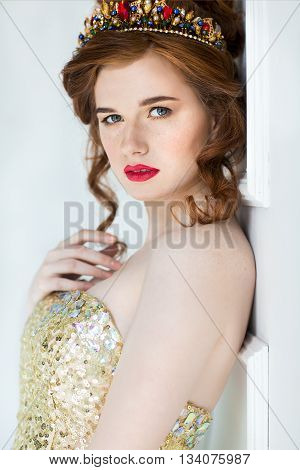 Beautiful redhaired fashion model posing in evening dress and in the diadem over light background