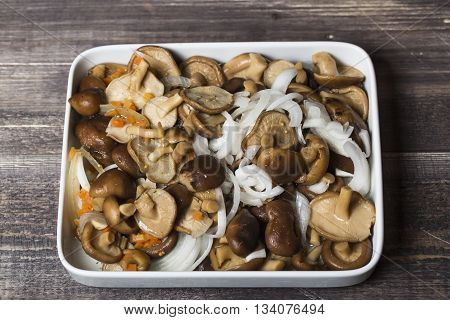 Marinated mushrooms with onion and carrots on white plate