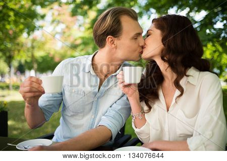 Happy couple drinking a cappuccino and kissing while sitting outdoors
